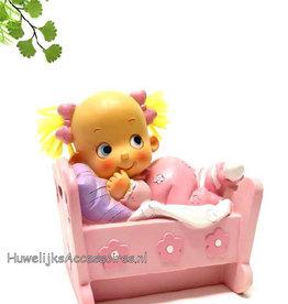 Meisje ligt in haar bedje met roze pyjama