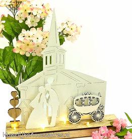 Bruidspaar kussen elkaar voor de kerk
