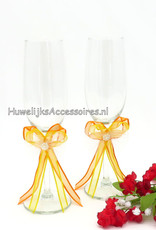 Huwelijk champagneglazen versierd met oranje en geel gekleurde strikjes