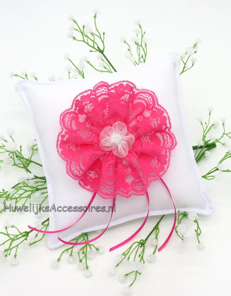 Witte trouwringen kussen met een fuchsia kanten rozet
