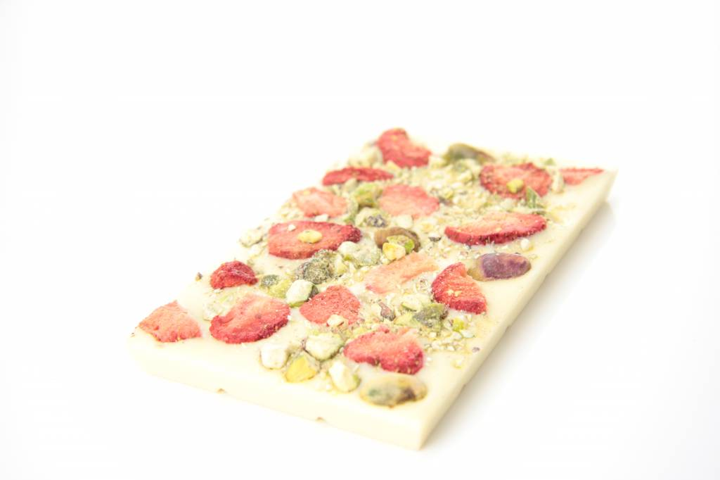 A bar of white chocolate with strawberry and pistachio nuts