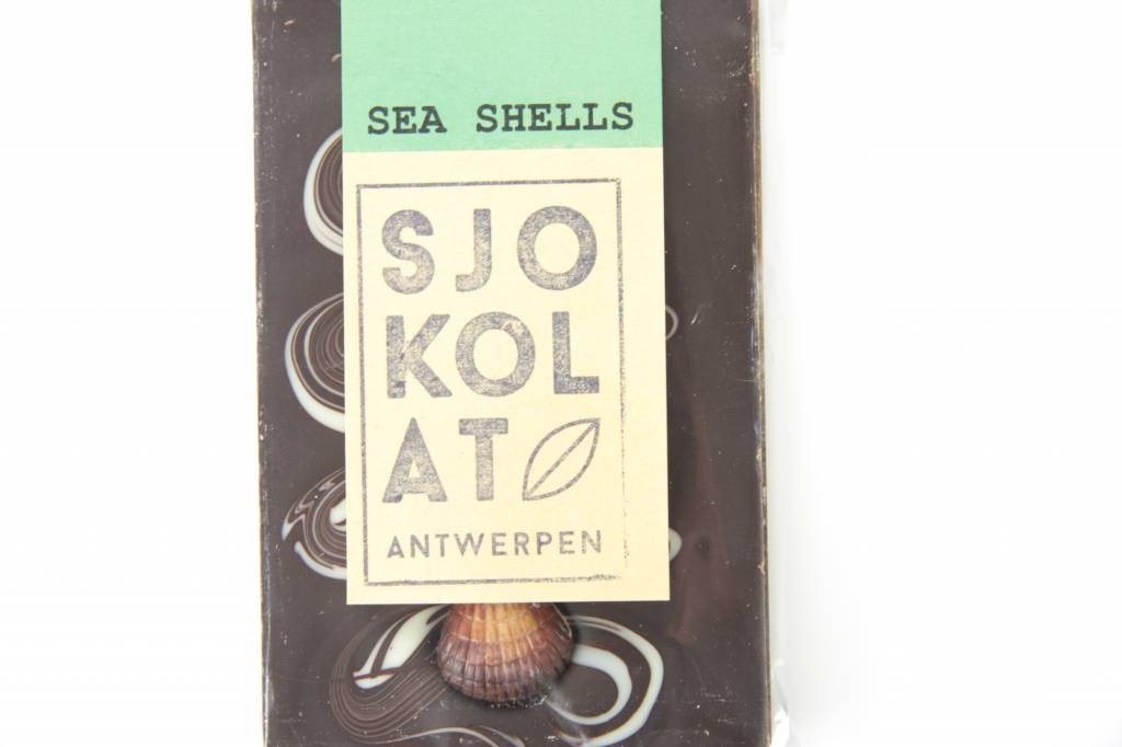 A dark chocolate bar with chocolate sea shells