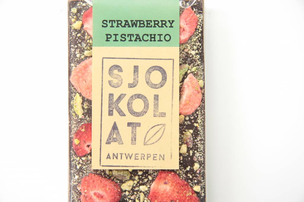A dark chocolate bar with strawberries and pistachio nuts