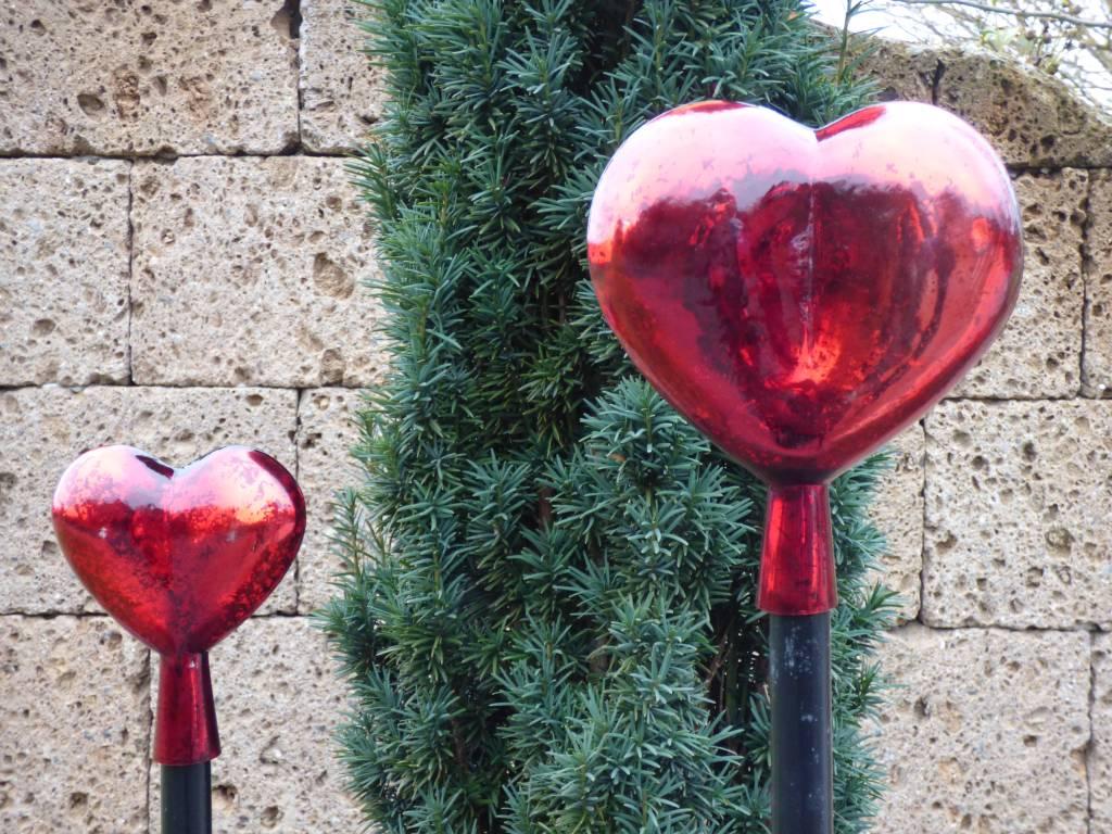 Strahlend rotes Herz aus Glas mit Holzstab