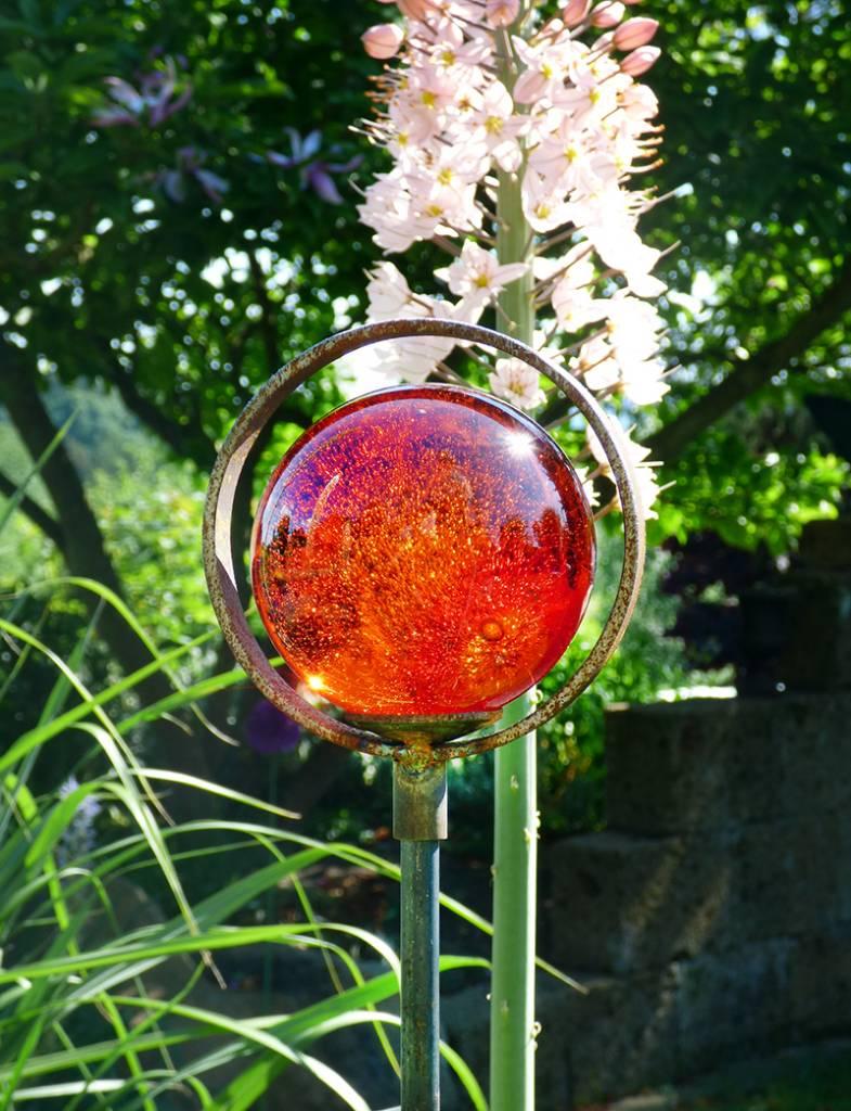 Strahlende Glaskugel mit Einschlüssen auf einem Dekostab mit Einfachring