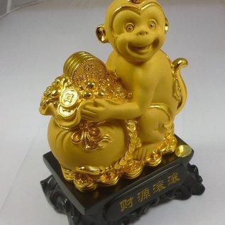Позолоченная обезьяна обнимающая переполненный монетами мешок как символ будущего процветания
