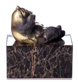 Lying panda bear made of bronze on a block of veined natural stone