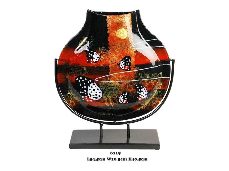 Estrecho jarrón decorativo en negro con rojo sobre soporte de metal