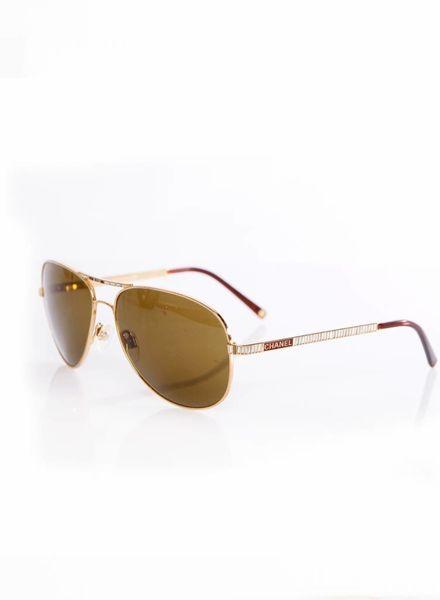 Chanel Chanel, pilotenbril met bruine glazen en stenen langs de pootjes en tussen de glazen.