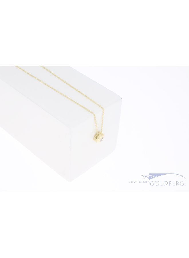 14k yellow gold circular pendant with zirconia on necklace