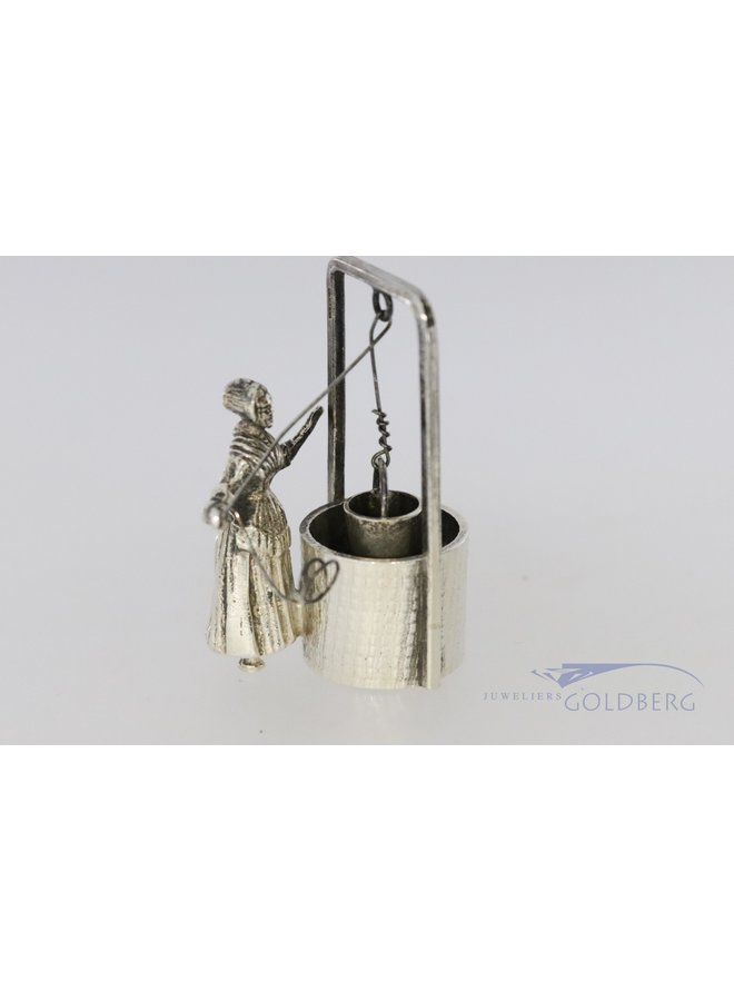 Miniature water well with woman.
