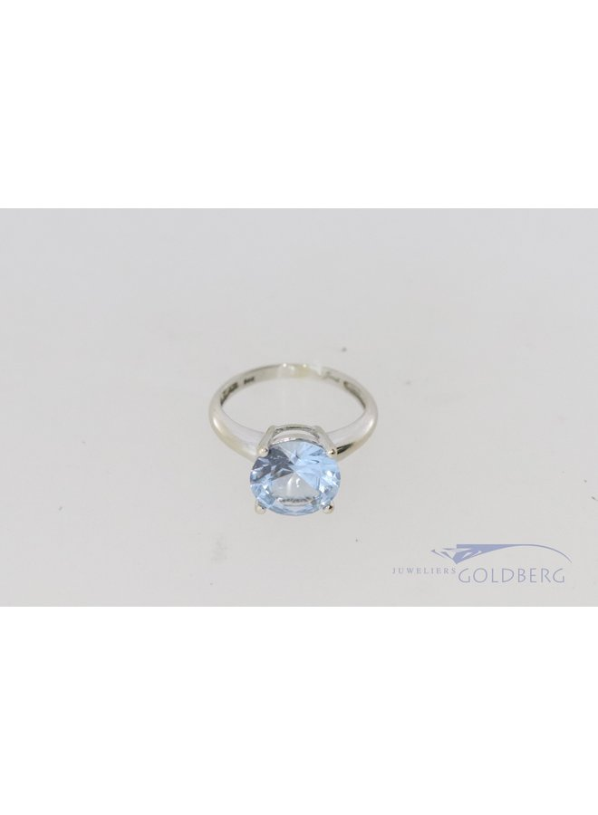 White gold ring with aquamarine-colored brilliant cut spinel.