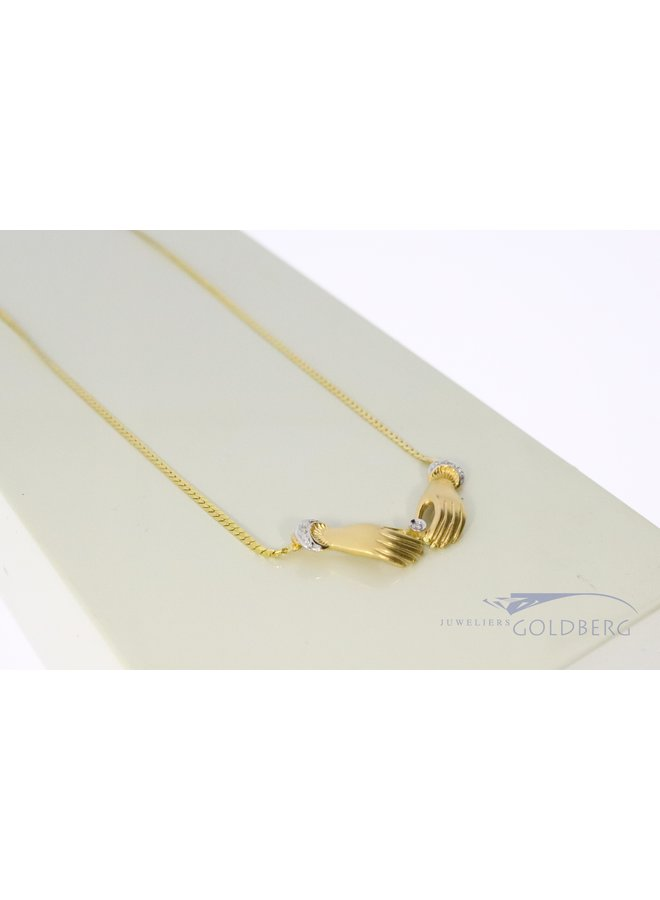 14 kt yellow gold mystical hands necklace.