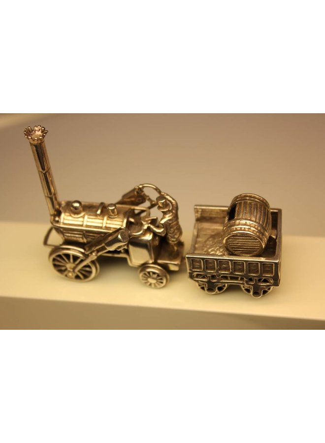 Miniature silver locomotive with coal wagon